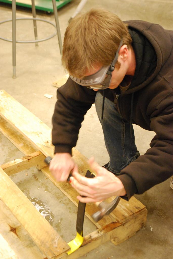 Deconstruction students disassemble wooden pallets as practice for deconstruction. REID HARMAN | THE HARBINGER