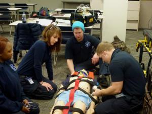 EMT students test out their skills on a mannequin.  ADAM BAKER | THE HARBINGER