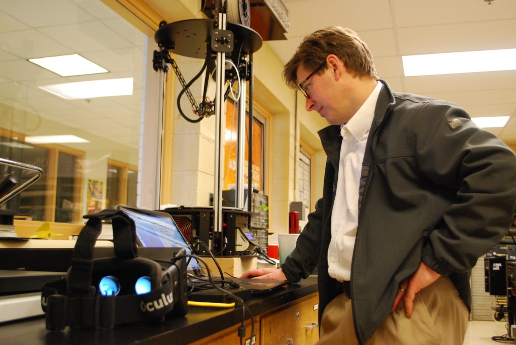 Between teaching classes, Professor John Baggett experiments with his new virtual reality goggles,left, and 3D printer, center back.