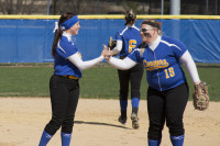 Rachel Patterson and Brittany Miller exchange congratulations on a good play. LAUREN MARRETT | THE HARBINGER