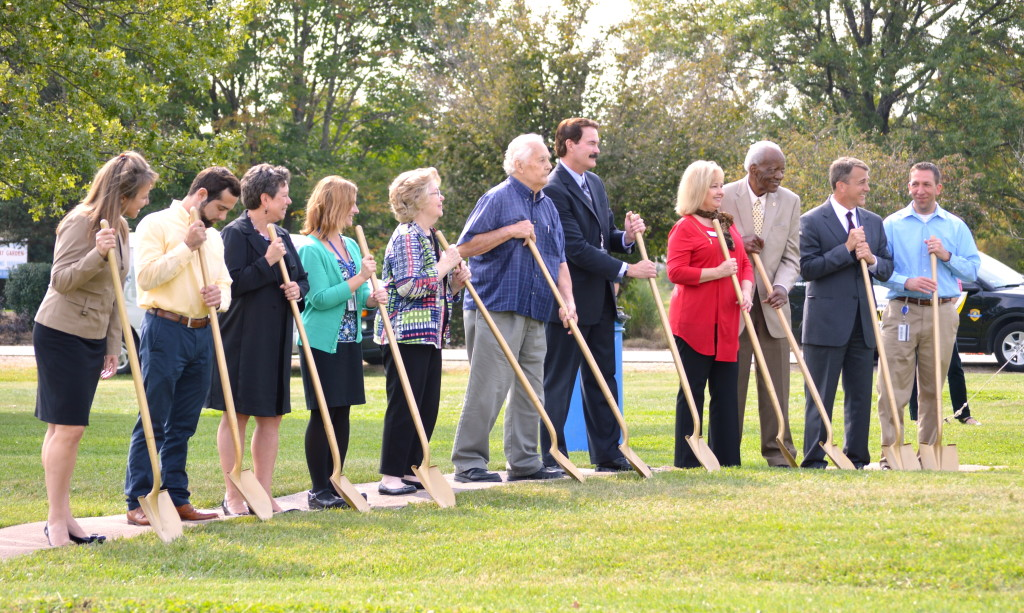 Moments after an employee in a mini excavator carried out the literal groundbreaking, ICC notables and guests posed with symbolic gold-painted shovels for photos. REID HARMAN | THE HARBINGER